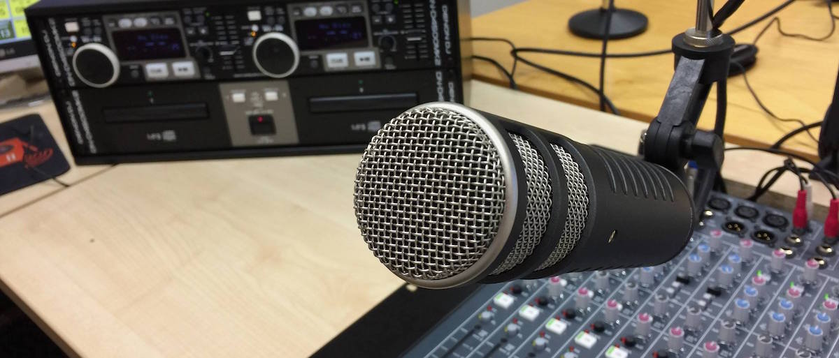 Microphone pointing towards the camera, with a mixer in the background