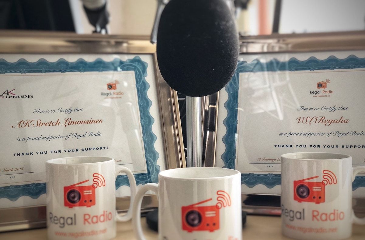 Two, framed certificates of Regal Radio sponsorship, surrounded by a microphone and Regal Radio mugs.