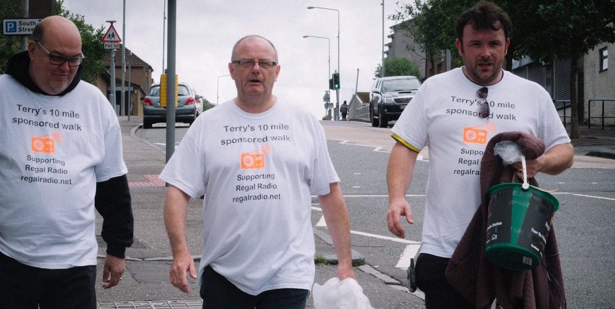 3 men walking along a road carrying money collection buckets.